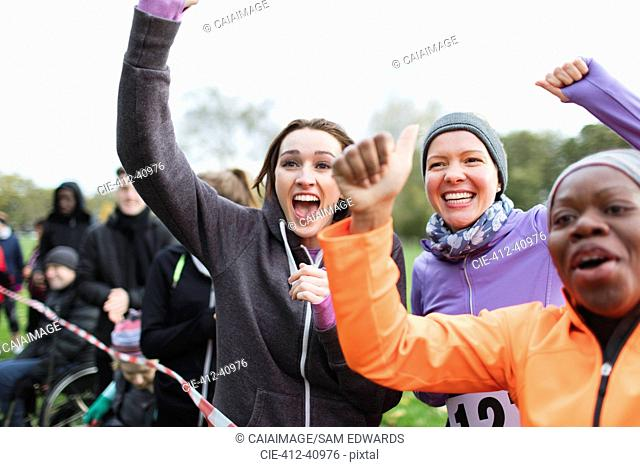 Enthusiastic female spectators cheering at charity run