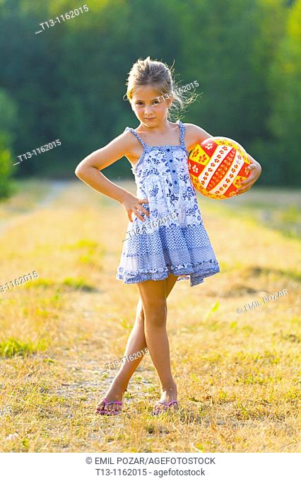 Posing with a ball in hand 6 years old girl