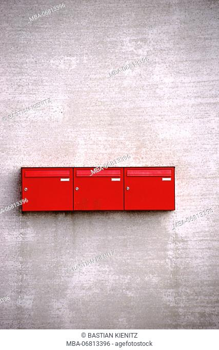 Three red mailboxes in a row on the rough concrete facade of a building