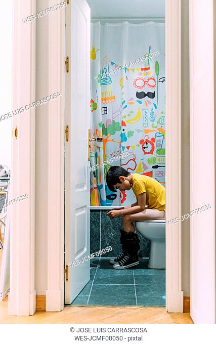 Boy playing video game on a games console, sitting on the loo