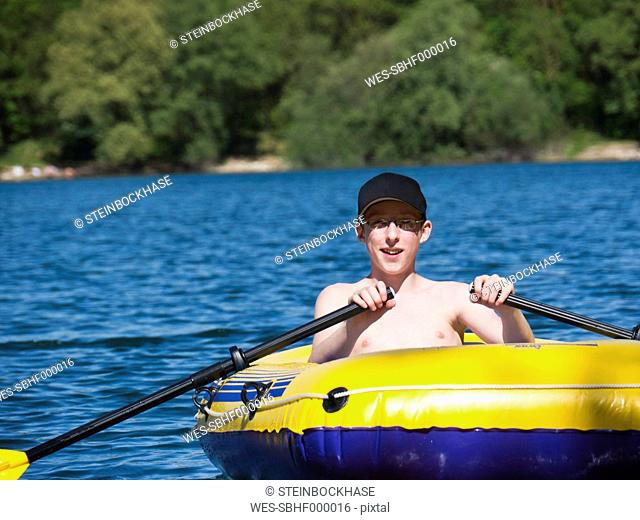 Germany, Bavaria, Mallertshofen, Boy in dinghy rafting at lake, smiling, portrait