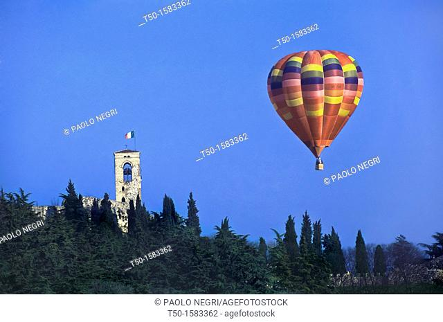 A hot air balloon flies over the bell tower with Italian Flag, Cavriana Mantova Lombardy Italy