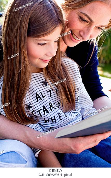 Mother and daughter reading book together, smiling