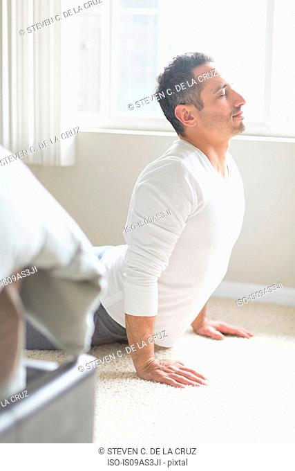 Mid adult man in yoga position