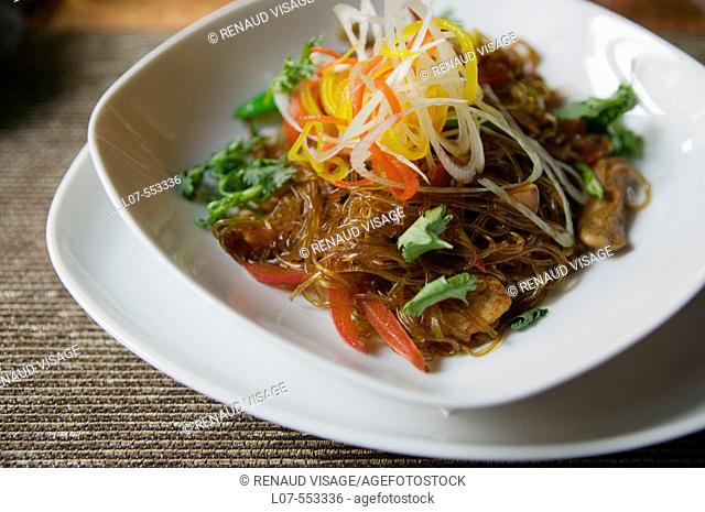 Transparent chinese noodles with shredded vegetables and mushrooms in fancy restaurant. St Petersburg. Russia