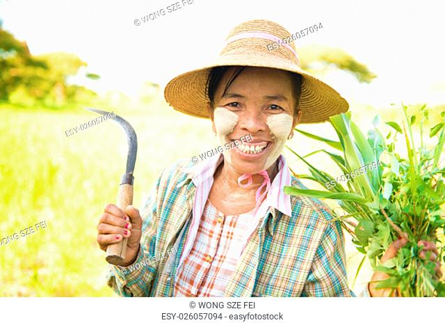 Portrait of a happy mature Burmese female farmer with thanaka powdered face who works in the field