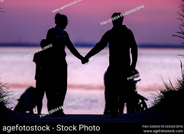 02 June 2020, Mecklenburg-Western Pomerania, Timmendorf (poel): A couple goes hand in hand after sunset on the beach on the island of Poel