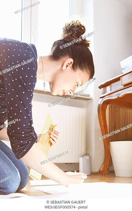 Young woman drawing pattern on the floor at home