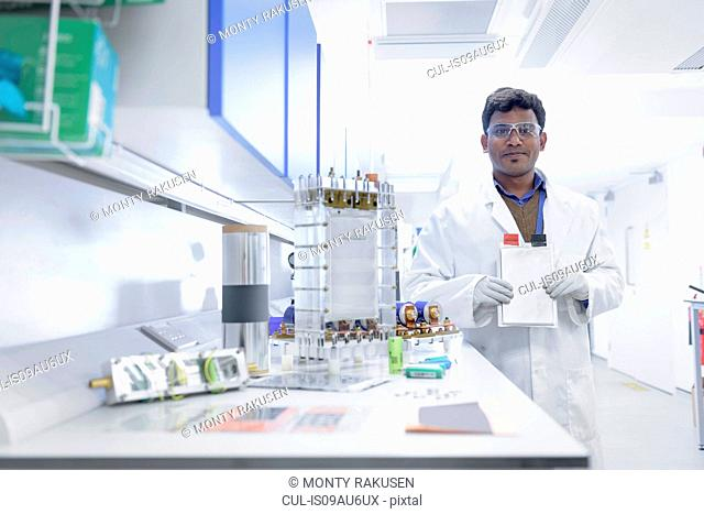 Portrait of scientist assembling lithium ion battery samples in battery research facility