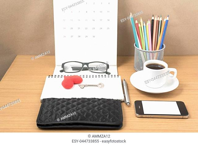 office desk : coffee with phone,wallet,calendar,heart,notepad,eyeglasses,color pencil box,key on wood background vintage style