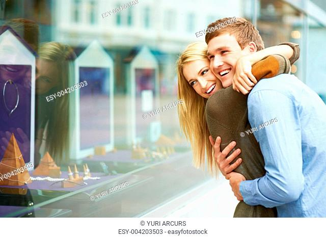 Lovely young couple embracing outside of a jewellery shop while laughing