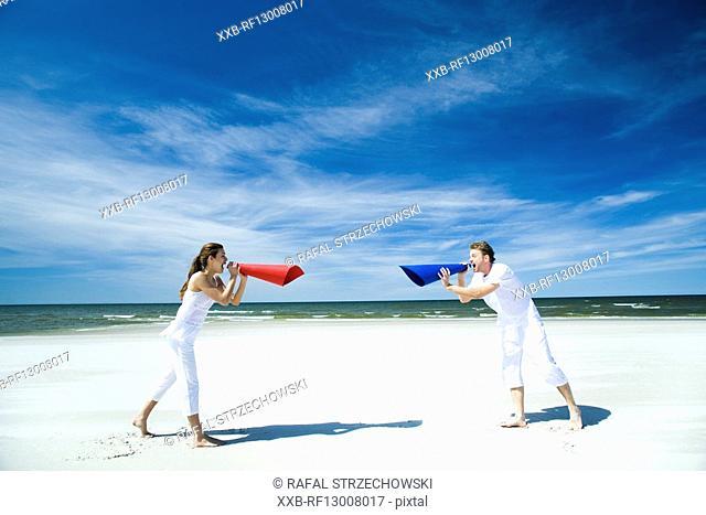couple with megaphones on beach