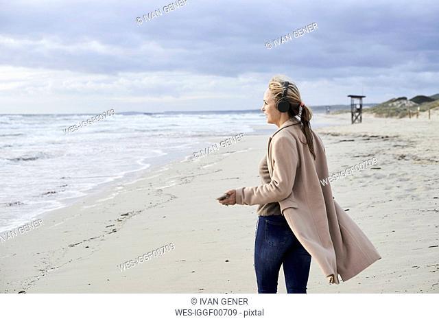 Spain, Menorca, senior woman using smartphone and wireless headphones on the beach in winter