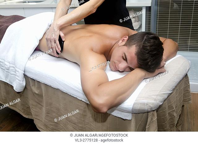 Smiling brunet in spa getting massage with hot stones