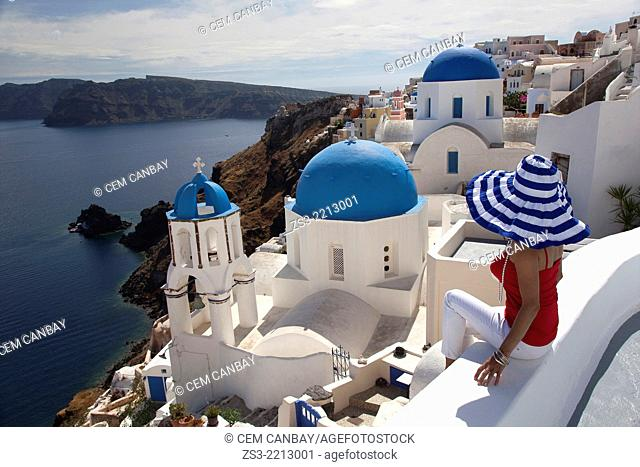 Woman in front of a blue domed church in Oia town looking at Caldera, Santorini, Cyclades Islands, Greek Islands, Greece, Europe