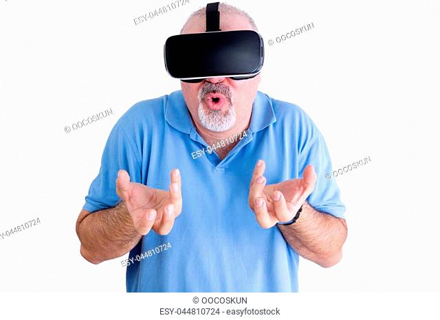 Man in blue polo shirt reacts to wearing virtual reality glasses by grabbing at the air with both hands and rounding his lips