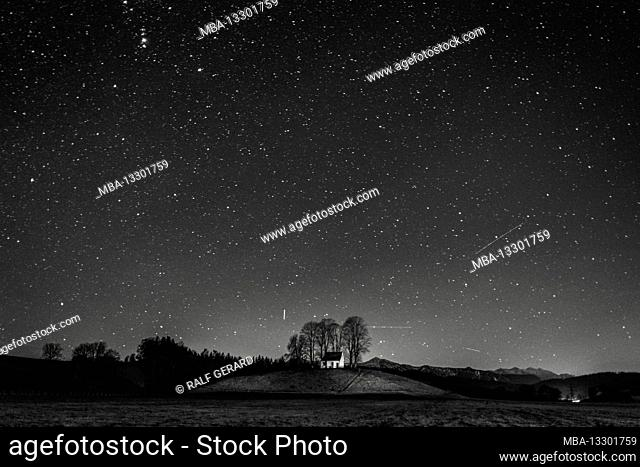 Germany, Bavaria, Antdorf, nocturnal chapel on a hill at the edge of the forest with a starry sky
