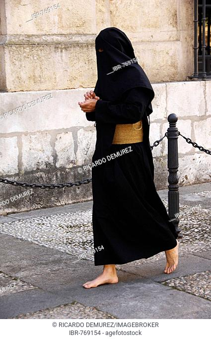 Penitent dressed in black penitential robe (nazareno) on their way to the Semana Santa, Holy Week Procession, Sevilla, Andalusia, Spain