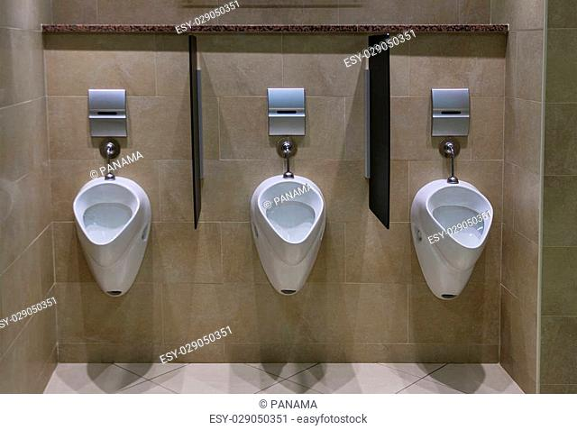 Set of urinals in a modern male toilet facility, with tiled floor and wall