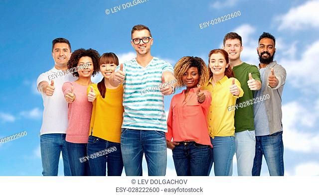 diversity, race, ethnicity and people concept - international group of happy smiling men and women showing thumbs up over blue sky and clouds background