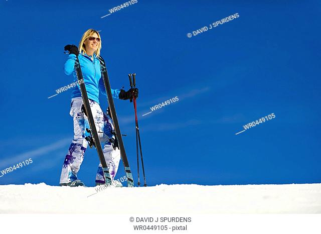 A woman stands on the ski slope with her skis
