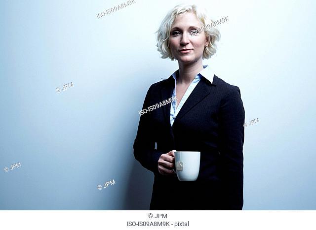 Studio portrait of blond businesswoman holding mug of tea