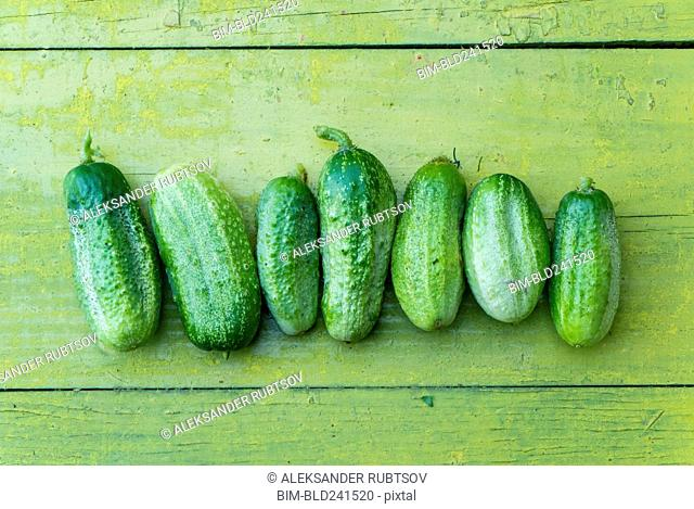 Green cucumbers in a row on wooden table