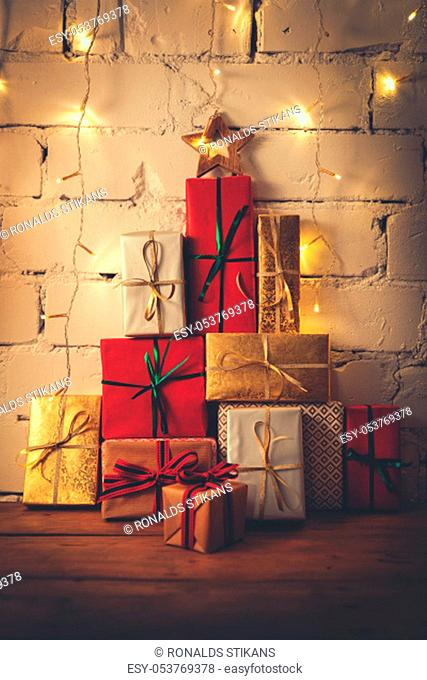 stack of christmas gifts on white brick wall background