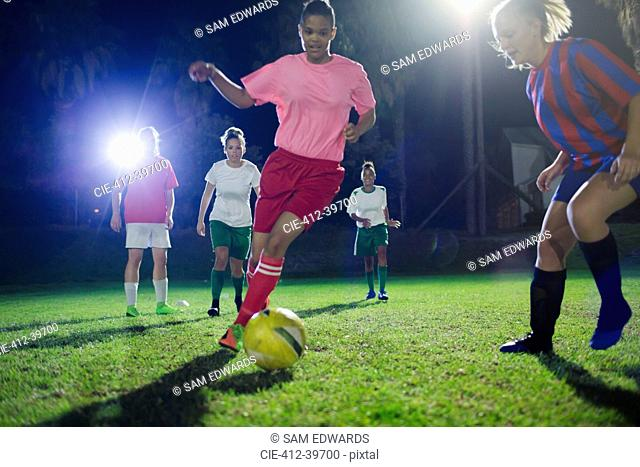 Young female soccer players playing on field at night, kicking the ball