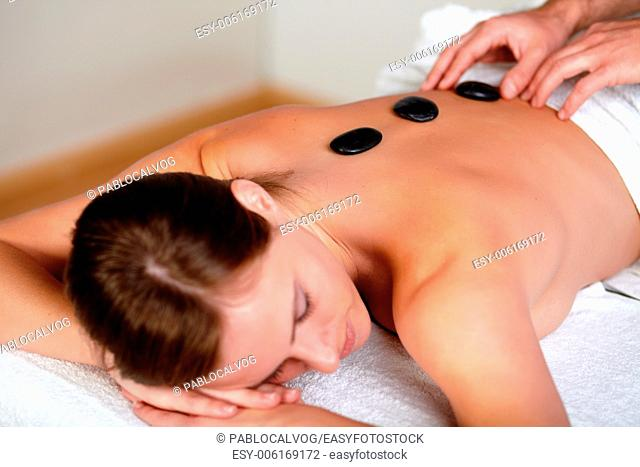 Close up portrait of a pretty woman relaxing face down having hot stones placed in a row down her back at a health spa