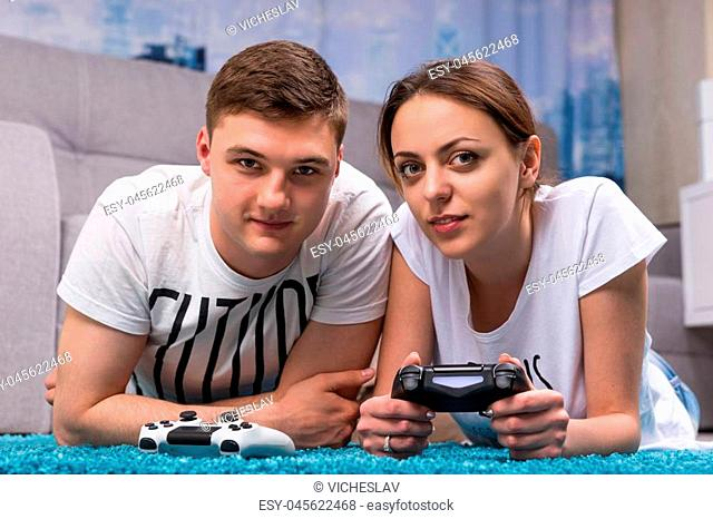 Happy couple lying on a rug in their living room playing video games looking towards the camera and pointing with fascinated expressions