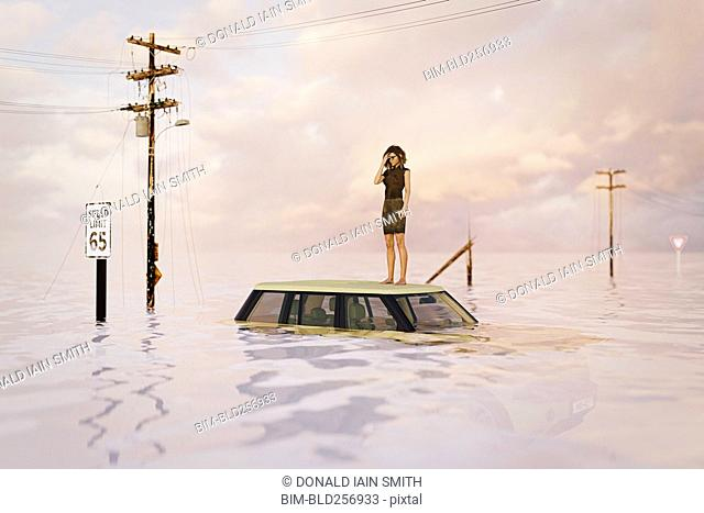 Woman standing on roof of car in flood