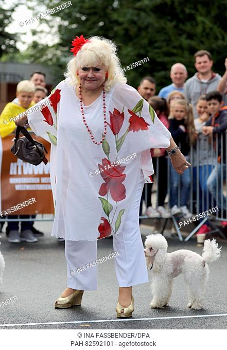 Jury member Eva Jacobs posing with her poodle Alexa during the fifth official World Handbag Throwing Championship (HTWWWM) at Movie Park Germany in Bottrop
