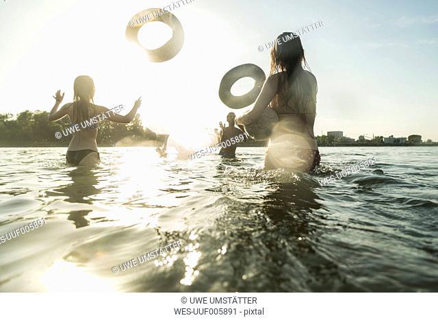 Happy friends throwing inner tubes in water