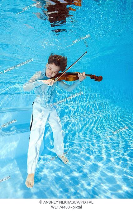 Boy playing the violin underwater