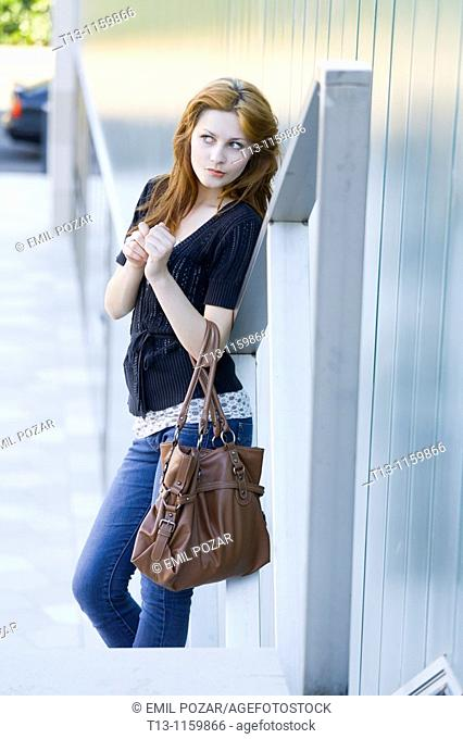 Curious with a purse in hand young woman