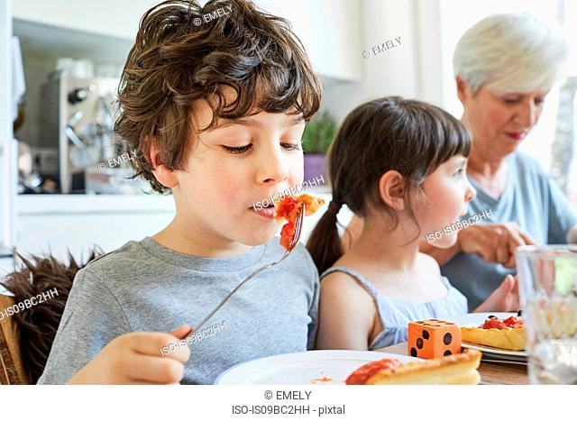 Young boy eating lunch at table with sister and grandmother