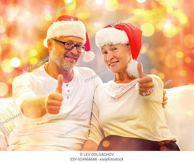 family, holidays, christmas, age and people concept - happy senior couple in santa helper hats sitting on sofa and showing thumbs up gesture over lights...
