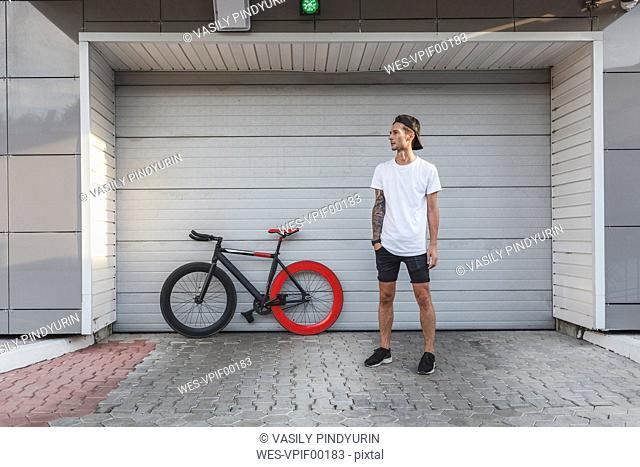 Young man with fixie bike at a roller shutter