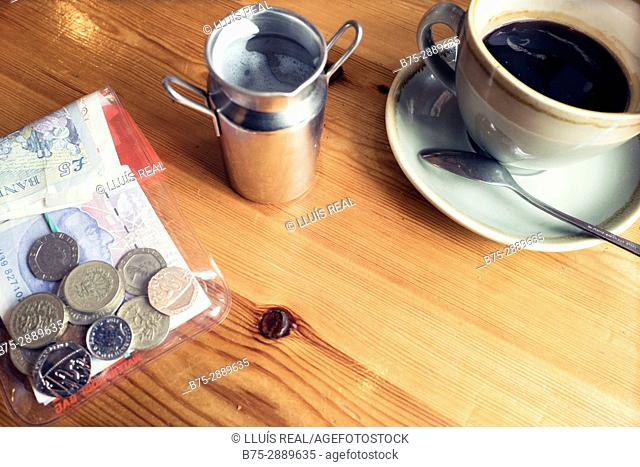 Still life with a cup of coffee, jug of milk and money. England
