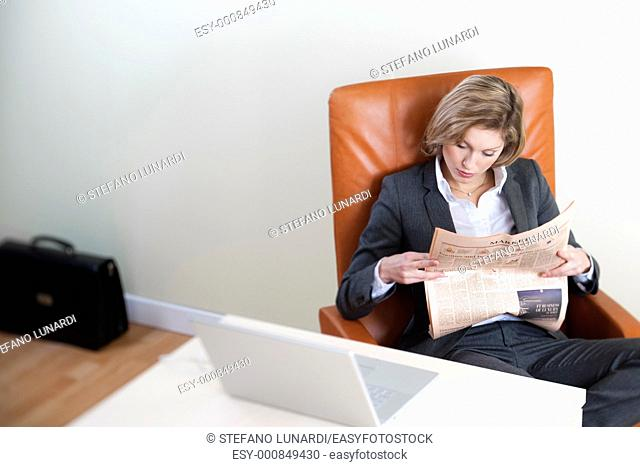 Business woman reading newspaper in her office, high angle view
