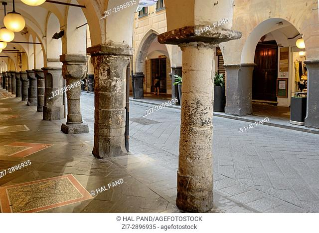 foreshortening of stone columns at old medieval covered walkway, shot at Mediterranean little town of Chiavari, Genova, Liguria, Italy