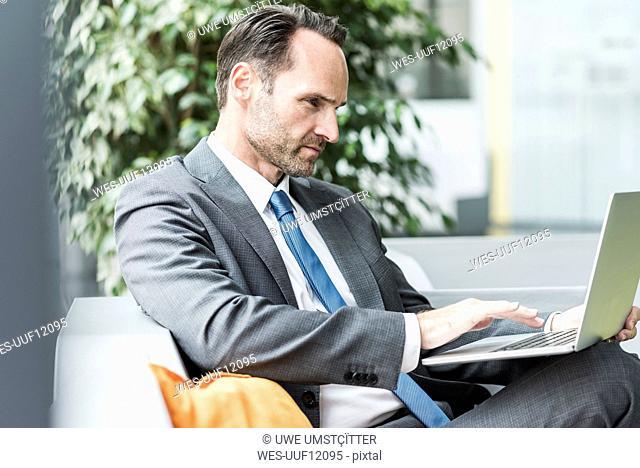 Businessman sitting in lobby using laptop