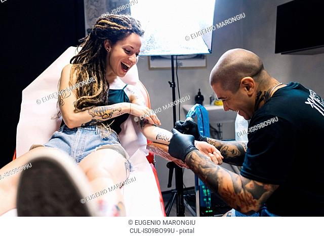 Tattooist drawing on arm of customer