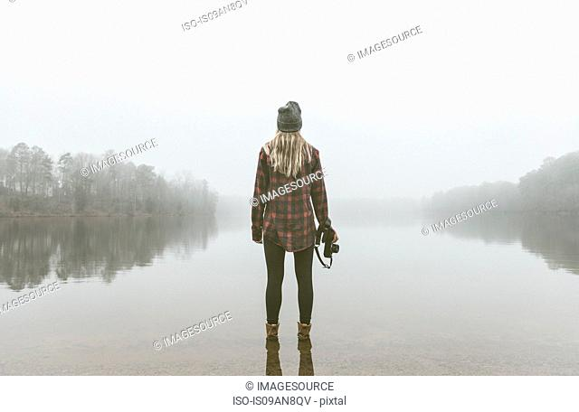 Young woman with camera standing in misty lake