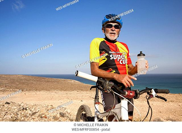 Spain, Canary Islands, Fuerteventura, senior man with mountainbike having a rest