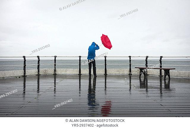 A man holding a red umbrella on Saltburn`s Victorian pier during a torrential summer downpour at Saltburn by the sea, North Yorkshire, England, United Kingdom