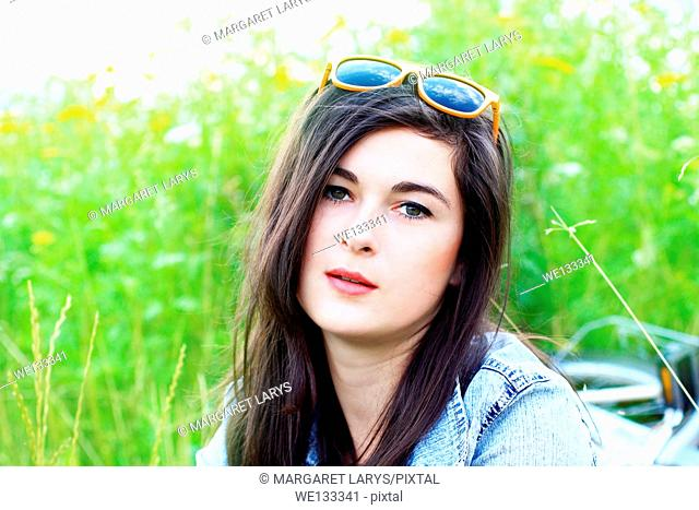 Beautiful young woman in summer fields, portrait