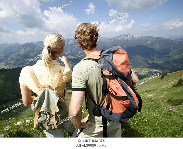 Couple looking out over valley, Kleinwalsertal, Allgau, Germany