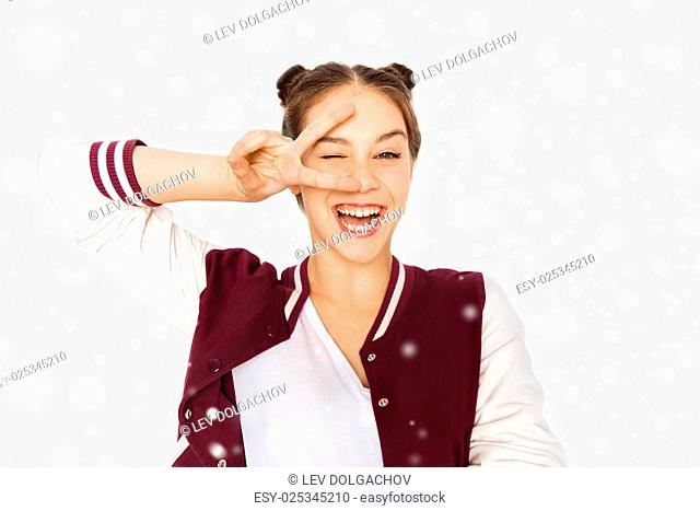winter, christmas, people, gesture and teens concept - happy smiling pretty teenage girl showing peace sign and winking over gray background and snow